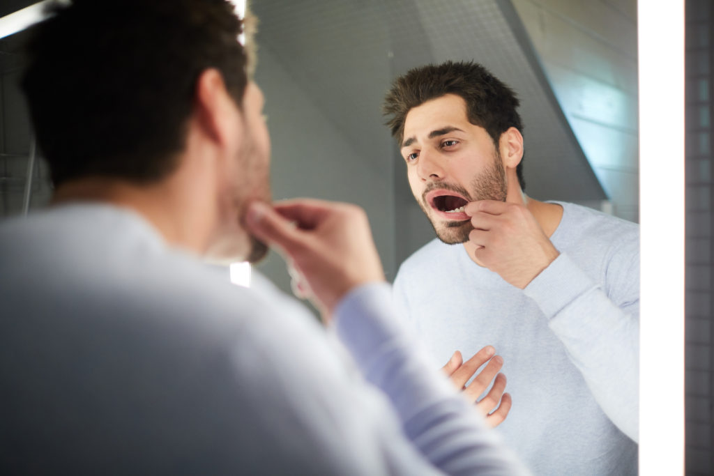 Young man checking tooth in bathroom